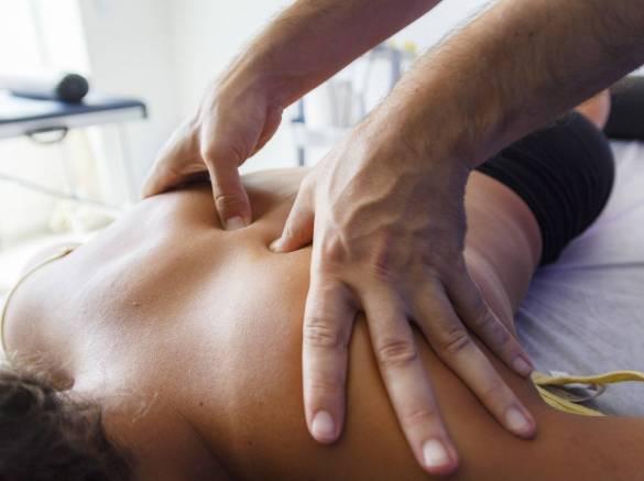 Fisioterapeuta trabajando los hombros de una joven deportista. Quiromasajista terapéutico trabajando. Tratamiento de sobrecarga muscular.