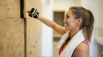 Beautiful girl in the dressing room at the gym opening her locker while smiling