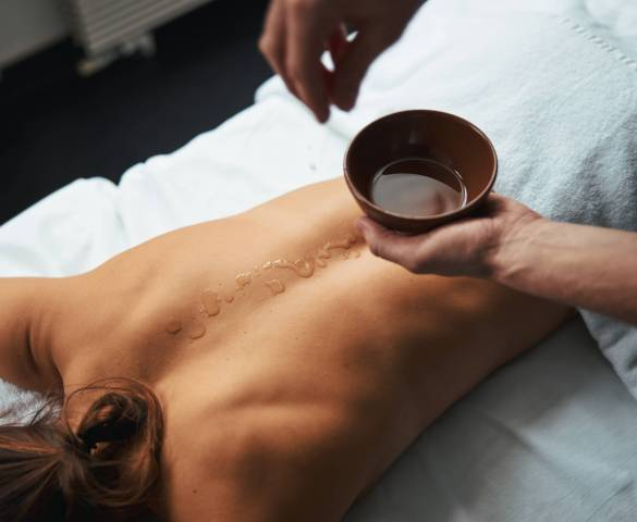 Pretty unrecognized female client lying on massage bed while massage therapist putting aroma oil on her back in spa salon