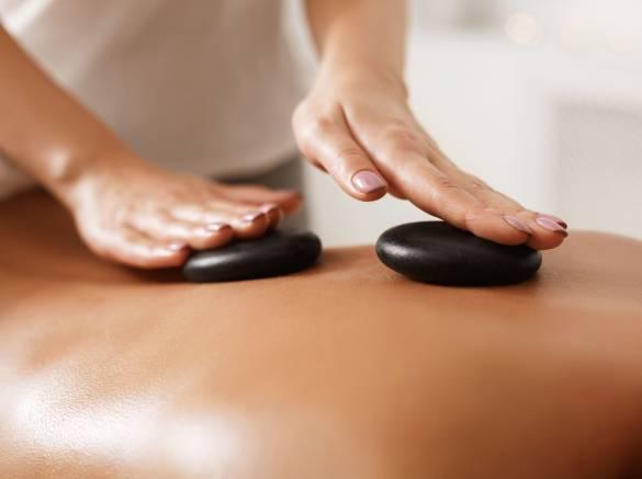 masseur-doing-back-hot-stone-massage-closeup-4NALQE2.jpg